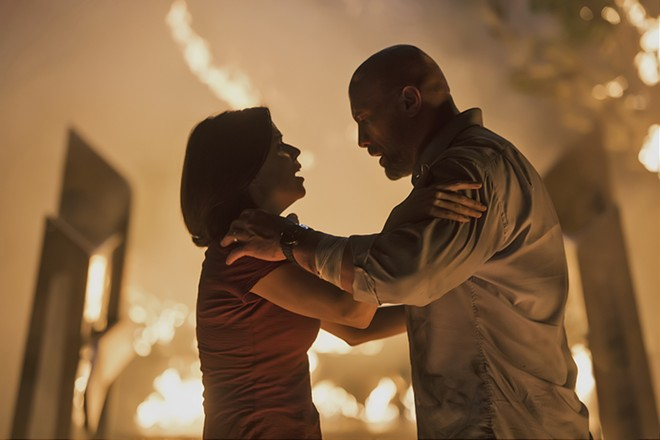 "This image released by Universal Pictures shows Neve Campbell, left, and Dwayne Johnson in a scene from ""Skyscraper."" - KIMBERLEY FRENCH/UNIVERSAL PICTURES VIA AP"