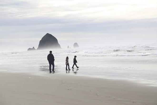 A family strolls near Haystack Rock. - RUTHIE PRASIL/PHOTO