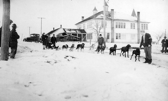 The dog sled team sent to rescue miner Rory Burke in 1930. Burke sits in the sled. From left behind the sled are Rory Burke's wife, unknown, Ida Weber and Sumner Stonebreaker.