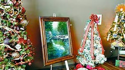 A painting by Vickie Broeckel is shown on display among decorated trees. They are part of the Festival of Trees and Art at the Center at the Whitman County Library in Colfax.