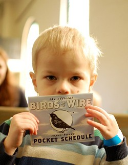 One of Larson Hicks' sons holds a schedule for Pullman's Birds on a Wire, a folk music festival that Hicks and his wife hosted and booked. Thirty-five bands played.