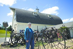 Artisans at the Dahmen Barn director Leslee Miller stands at the barn's famous Wheel Fence in Uniontown. - DEAN HARE