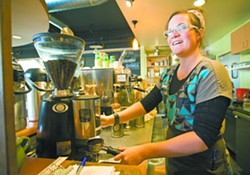 Barista Grace Zeller talks to a customer while making a latte at the Moscow Food Co-op on Tuesday. - GEOFF CRIMMINS
