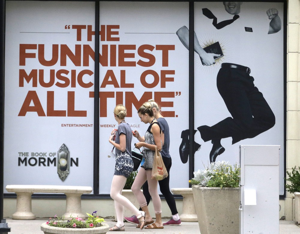 """People walk past signs announcing the """"Book of Mormon"""" musical at the Capitol Theatre, Monday, July 27, 2015, in Salt Lake City. The biting satirical musical that mocks Mormons is finally coming to the heart of Mormonlandia, starting a sold-out, two week run on Tuesday, July 28, 2015, at a theater two blocks from the church?s flagship temple and headquarters. - AP PHOTO/RICK BOWMER"""