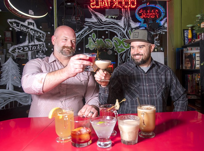 Hogan's Pub owner/bartender Skate Pierce (left) and bartender Gary Burleson cheers while sitting in front of an array of seasonal drinks they created for December. - TRIBUNE/PETE CASTER