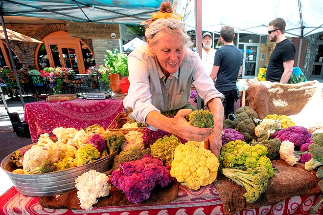 A woman organizes colorful cauliflower at her stand at a past Moscow Farmers Market. It returns Saturday for customer foot traffic, with strict distancing rules. Pete Caster/Lewiston Tribune - PETE CASTER/TRIBUNE FILE PHOTO