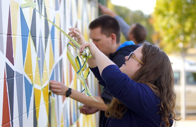Taylor Ransom removes tape from a new mural on the side of the Art and Architecture East building Thursday afternon. The mural was designed by University of Idaho student Danielle Cappelli. - KAI EISELEIN
