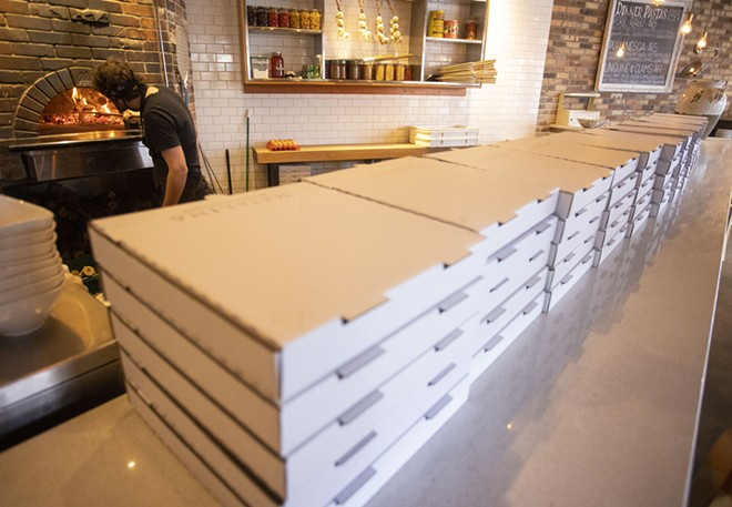 Ivan Saueracker puts a log on the fire in the pizza oven at Maialina on Thursday in Moscow. Pizza boxes for take-out orders are stacked on the counter. - AP