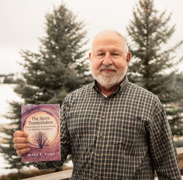 "Mark F. Yama holds a copy of his book, ""The Spirit of Transcendent: Exploring the Extraordinary in Human Experience"" Dec. 29, 2020 at his home in Troy. - PHOTO DENE HARE"
