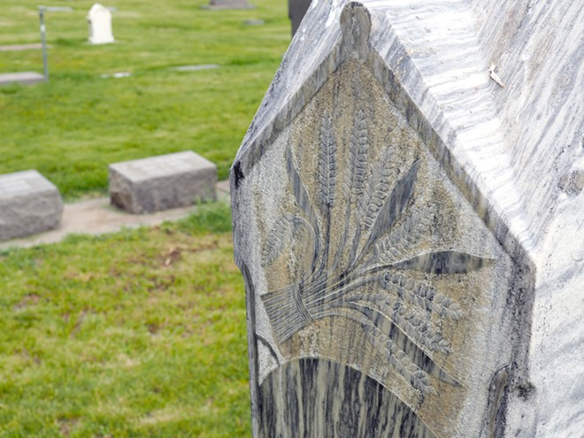 A sheaf of wheat is engraved on a headstone in the Colfax Cemetery. Tara Roberts/for Inland 360 - TARA ROBERTS/INLAND 360