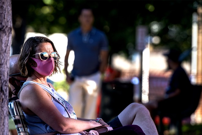 Shawna Pearson wears a mask as she listens to music at Sound Downtown at Brackenbury Square on Friday. - PHOTO/AUGUST FRANK