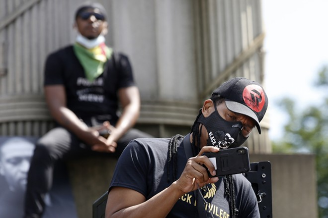 A man uses his cell phone to record speakers as another listens from the pedestal of a column during a Caribbean-led Black Lives Matter rally at Brooklyn's Grand Army Plaza, Sunday, June 14, 2020, in New York. - AP PHOTO/KATHY WILLENS