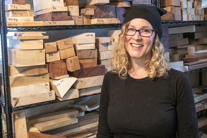 """Former scientist turned artist Kristin LeVier, of Moscow, poses for a picture in front of a storage of her artwork materials consisting of mostly wood and cardboard. """"Cardboard boxes are like gold to woodworkers,"""" said LeVier. - ZACH WILKINSON"""