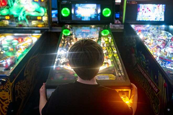 The flashing lights of the Jurassic Park pinball machine silhouette Patrick Martin, 6, as he enjoys his time in front of the classic arcade staple on Friday afternoon at Arcade1upclarkston. - PETE CASTER/360