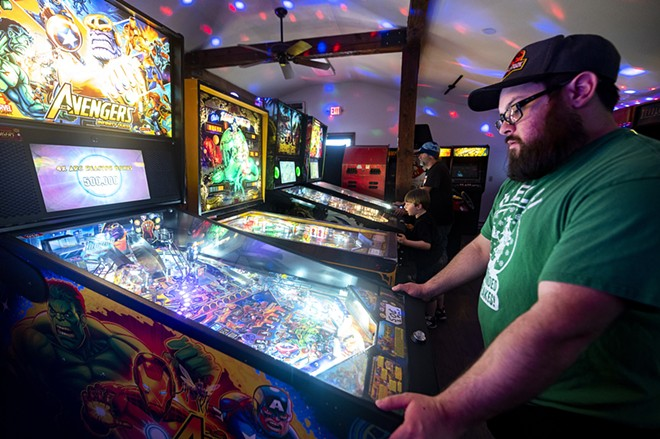 Brian Boles, of Lewiston, right, plays pinball alongside his son, Patrick Martin, 6, and Richard Stover, owner of Arcade1upclarkston, on Friday afternoon in Clarkston. - PETE CASTER/360