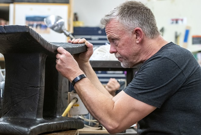 """Virgil Aurand observes the grooves on a piece he calls """"Elm Bench,"""" which was carved from a single log and then burned in a traditional Japanese style of preserving wood known as Shou Sugi Ban. - ZACH WILKINSON/360"""