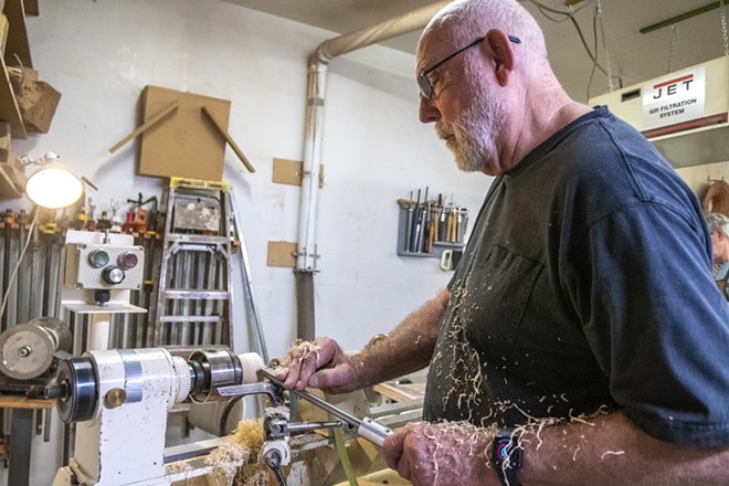 Covered in saw dust, Jim Christiansen makes a wooden bowl using a gouge while turning it on a lathe at the Palouse Woodworkers Collaborative in Moscow. - ZACH WILKINSON/360