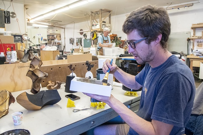 """Ben Carpenter applies a coat of paint to a piece he calls """"Ax Oxe."""" The project involves multiple layers, and Carpenter drilled holes into individual pieces so that they can fit into one another upon presentation. - ZACH WILKINSON/360"""