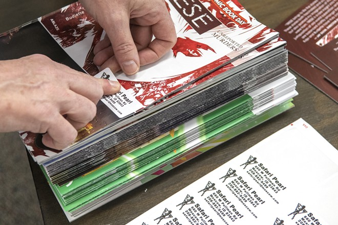 Safari Pearl owner Katherine Sprague adds labels to comic books that will be given away as part of Free Comic Book Day. - ZACH WILKINSON/INLAND 360
