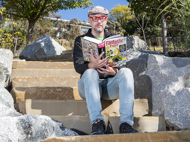 """Roger Whitson, an associate professor of English at Washington State University, holds a Fantastic Four volume one omnibus while posing for a portrait on a set of steps at the University of Idaho Arboretum and Botanical Garden on Friday afternoon, Oct. 1, 2021. """"I've always read comics, it's like a comfort food to me,"""" said Whitson. - ZACH WILKINSON/INLAND 360"""