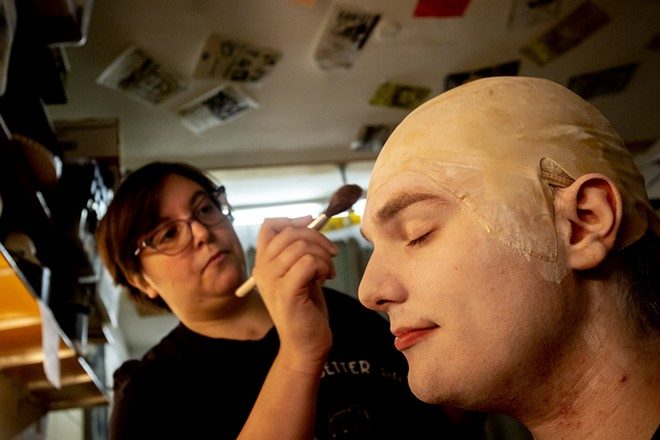 Gabi Segren applies makeup to Aven Sparkman, playing Uncle Fester, before a rehearsal for the Addams Family at the old Lewiston High School on Monday evening. - AUGUST FRANK/360