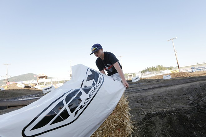 12 year old Mayson Whittaker places a sponsor cover on a hay bale before the 14th Annual Moto X. - YOUNG KWAK