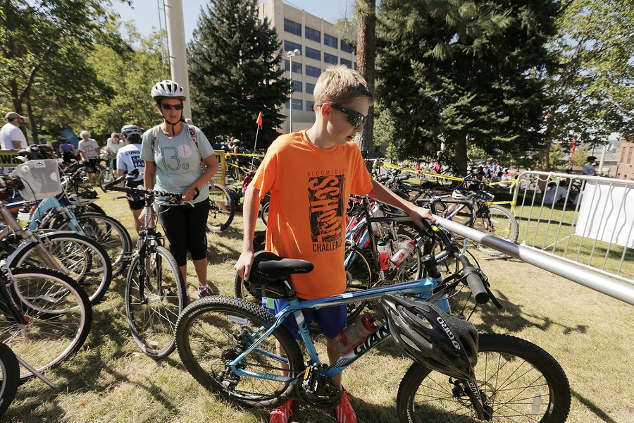 13 year old Jacob Bennatt, right, places his bicycle into the bike corral as his mother Suzanne looks on after they finish the REI 21 Mile River Loop route. - YOUNG KWAK