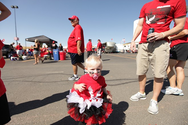 15 month old Madison Maupin, center, walks in the parking lot with her father Jeramie, right, before the game. - YOUNG KWAK