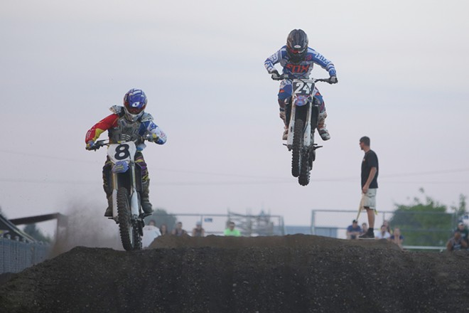 250 cc junior amateur rider Derek Donoian (8), from Rathdrum, Idaho, and 15 year old 250 cc intermediate amateur rider Riley Anderson (24), from Kila, Mont., take a jump in a Moto 1 race. - YOUNG KWAK