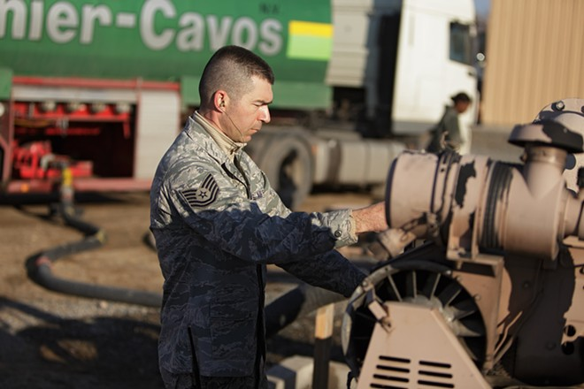 376th Expeditionary Logistics Readiness Squadron Technical Sergeant Nick Parrott starts up a R22 pumping unit to move diesel fuel from a delivery truck to a storage bladder. - YOUNG KWAK