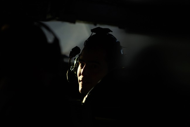 376th Expeditionary Operations Group Co-Pilot Captain Mike Dobbs looks towards the cabin inside a KC-135. - YOUNG KWAK