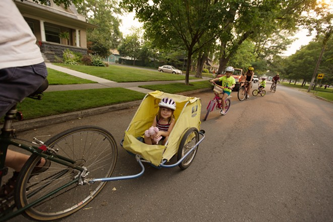 Five-year-old Carmen Walter, center, rides in a trailer as her father Jeff pedals, with the rest of the family following. - YOUNG KWAK