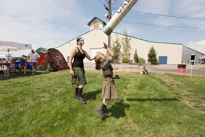 Six-year-old Connor McKinney, center, throw a caber as Sabin McKinney looks on. - YOUNG KWAK