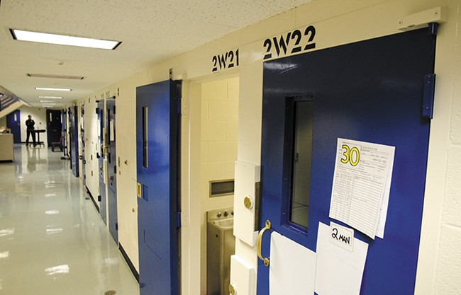 "A corrections officer stands at the end of the ""suicide watch"" cell corridor at the Spokane County Jail. - JACOB JONES"