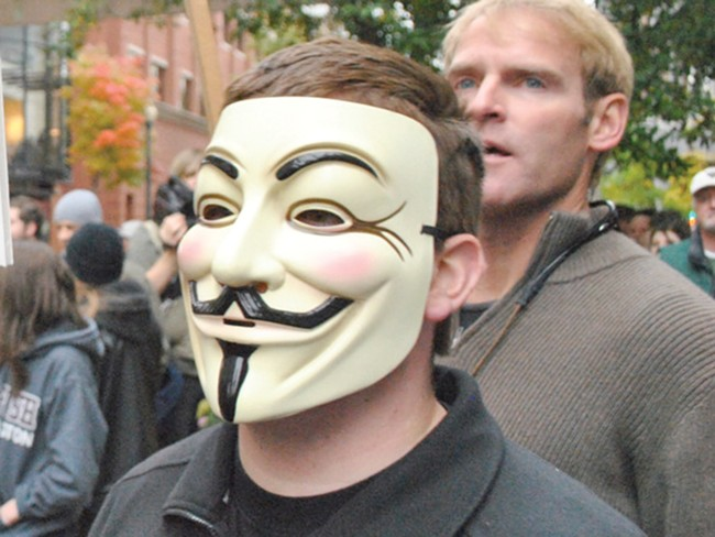 A man wearing a Guy Fawkes mask during an Occupy Spokane march in October - CHRIS STEIN