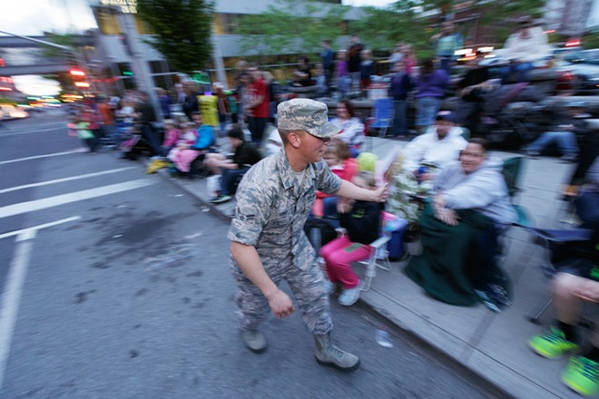 A member of the Washington Air National Guard 141st Refueling Wing high-fives spectators. - YOUNG KWAK