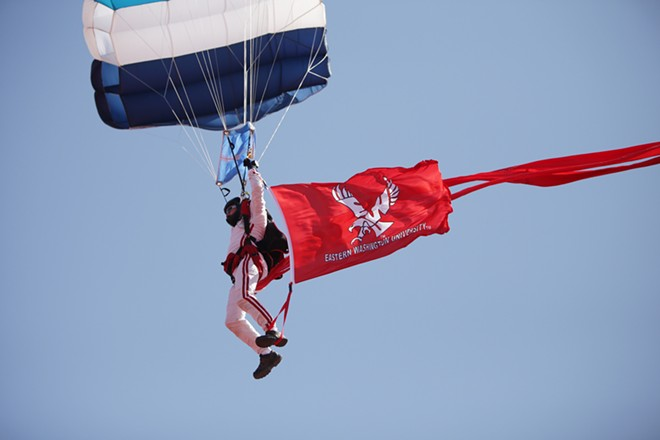 A member of West Plains Skydiving approaches Roos Field before the game. - YOUNG KWAK