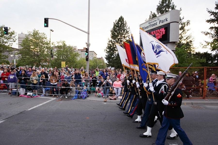 A military color guard marches past spectators. - YOUNG KWAK