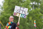 A participant holds a sign saying 'It gets Better' at the Pride Parade.