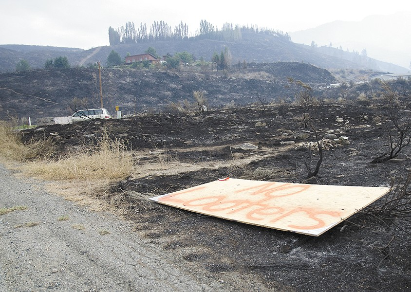 "A plywood sign reads ""No looters"" along Highway 153 in the Methow Valley, where many homes were destroyed by the Carlton Complex Fire. - JACOB JONES"