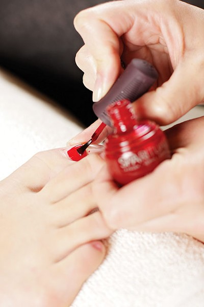 A Spa Paradiso nail technician brushes on beetle-free SpaRitual polish. - YOUNG KWAK