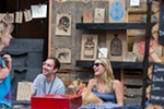 Aaron Abolofia of Tiny Mammoth Ink, left, sits with his friend Melissa Estma and dog Lola at his booth.