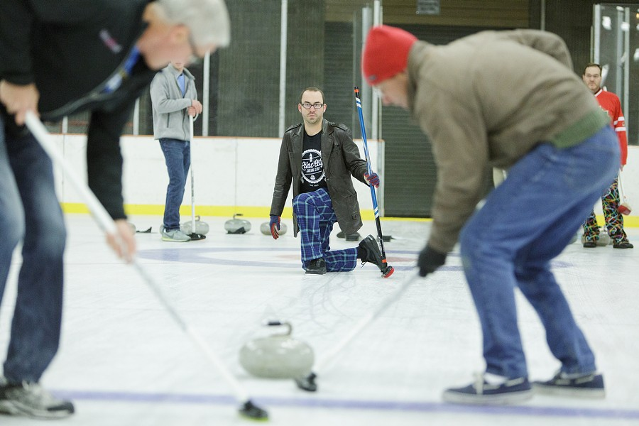 After throwing a rock, Lilac City Curling Club member Jon Escott, center, watches students Dave Jackson, left, and Jerry Schmidt sweep. - YOUNG KWAK
