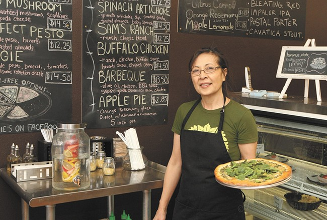 Allie's Vegan Pizzeria owner Atania Gilmore with her spinach artichoke pizza. - MEGHAN KIRK