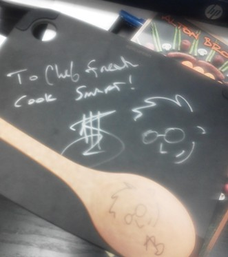 """Brown signed Kyle Bowlby's (his nickname is """"Chef Freak"""") cutting board and spoon since the Wandering Table sous chef couldn't attend the show last night."""