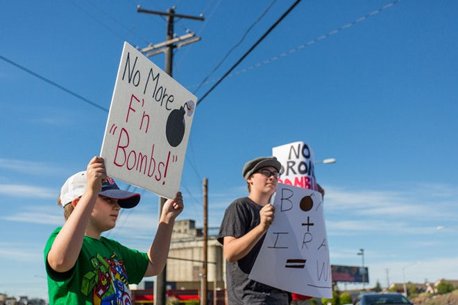 Andon Webster, left, and older brother Russell Webster, right, protest against the threat of bombing Iraq. - MATT WEIGAND