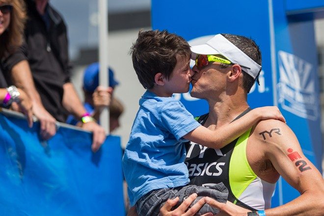 Andy Potts is met by his son at the finish line after winning the Coeur d'Alene Ironman. - MATT WEIGAND
