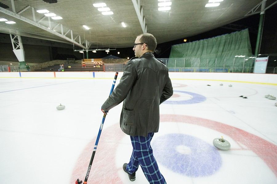 As a skip, Lilac City Curling Club member Jon Escott walks toward the location in the house he wants a rock to be thrown. - YOUNG KWAK