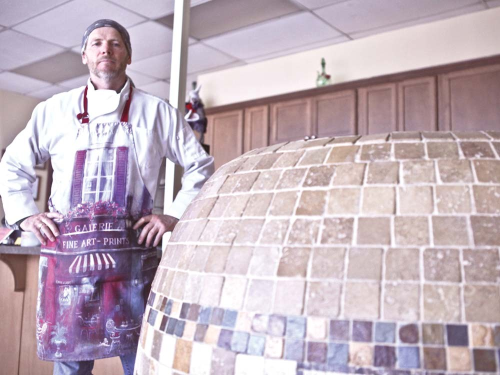 Asian Cafe owner Andrey Chumov stands beside the tandoor oven in which he makes meat-filled pastries or samsas. - JORDAN BEAUCHAMP
