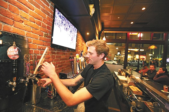 Bartender Levi Alford pours a beer at Post Street Ale House. - YOUNG KWAK